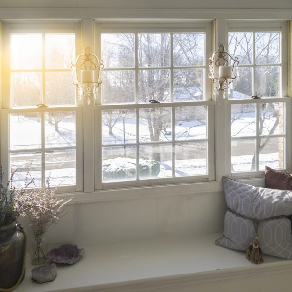 Photo taken inside a home showing a glass window . Snow and winter scene on outside.