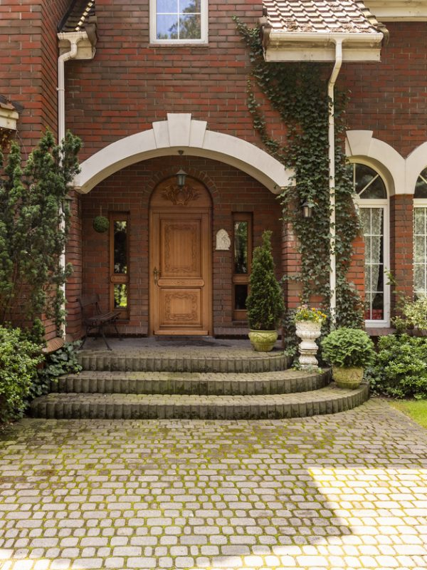 Cobbled path and steps leading to a stylish entryway with ornamented wooden door and side windows in a red brick English style mansion.
